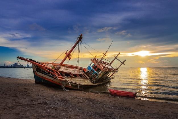 美しい夕暮れの空で海岸に残骸が残っていた。
