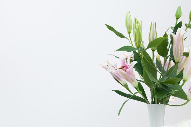 白い背景に白い花瓶に白いユリの花束