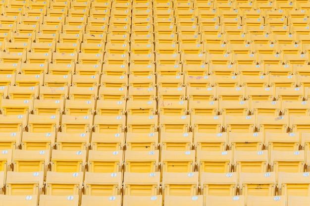 スタジアム、サッカースタジアムの座席の行で空の黄色い座席、フォーカスを選択