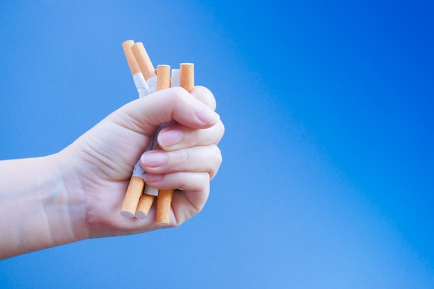 Сломанная сигарета на руке. победа с зависимыми от никотина проблемами. не курить. выход из наркомании концепции.