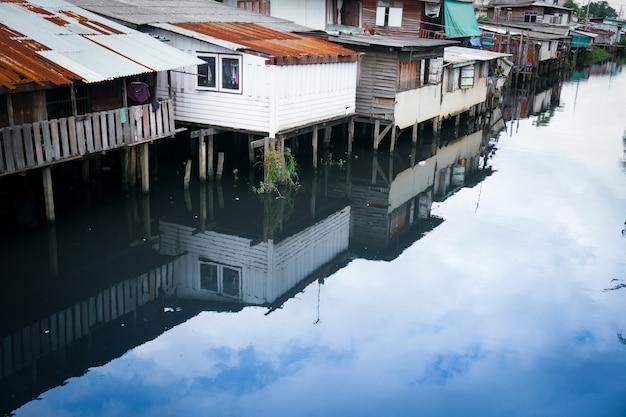Небольшие дома, трущобы возле канала. старая община на берегу реки в таиланде.