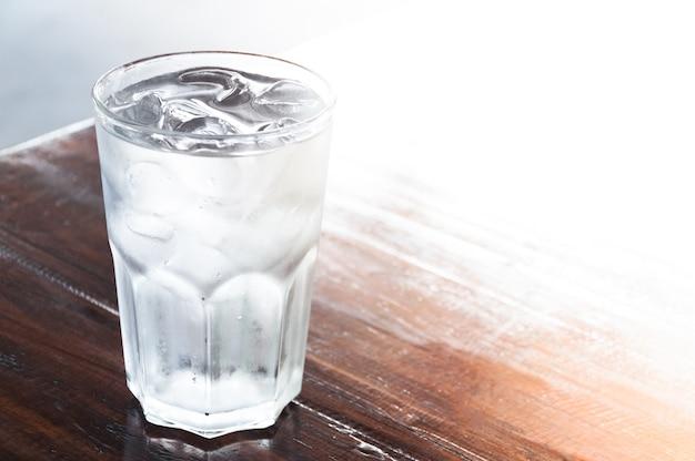 木製のテーブルに氷の水のガラス