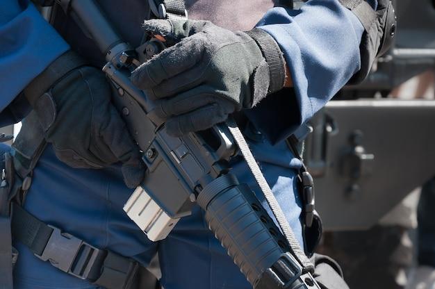 自動銃で機械を保持している兵士。軍事行動の準備。保護具に身を包んだ兵士