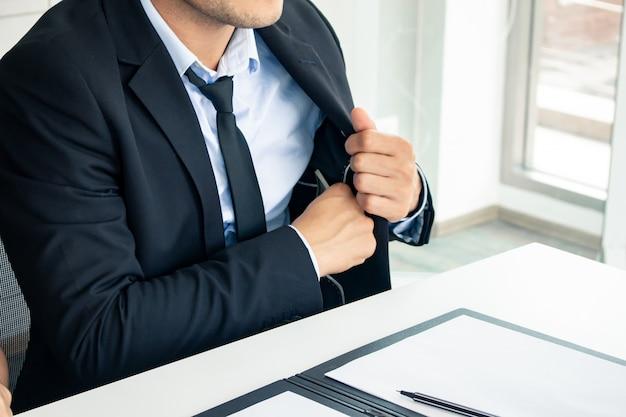 実業家は彼のスーツからお金を引き出しています。