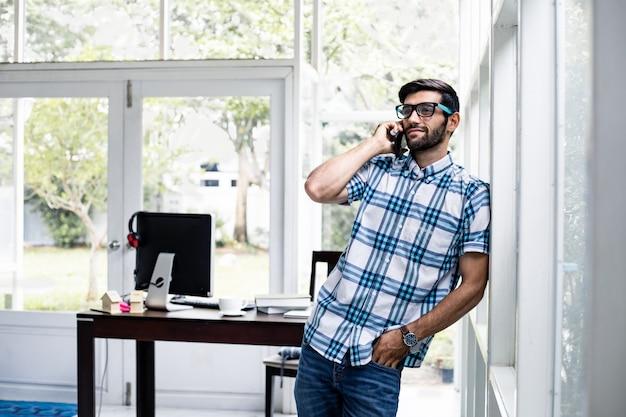 若い男が自宅で仕事をするために携帯電話で会社の仕事について話している。