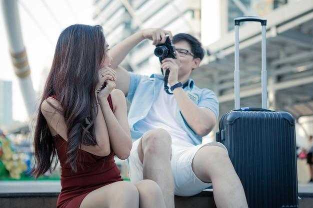 若い男は幸せに一緒に旅行しながら彼のガールフレンドを撃った。