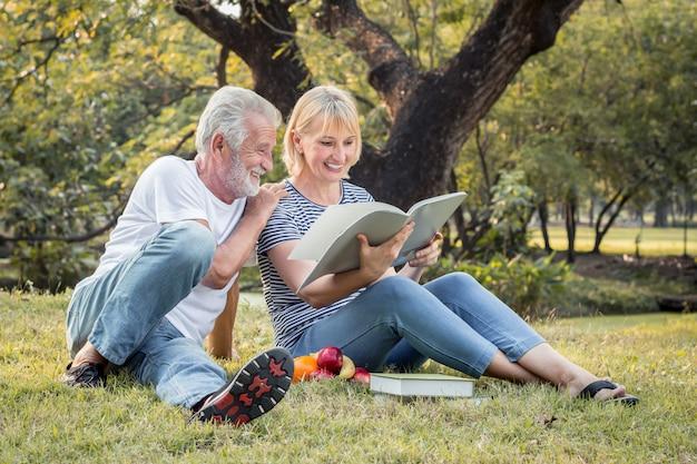 Дедушка и бабушка читают книгу, сидя на траве.