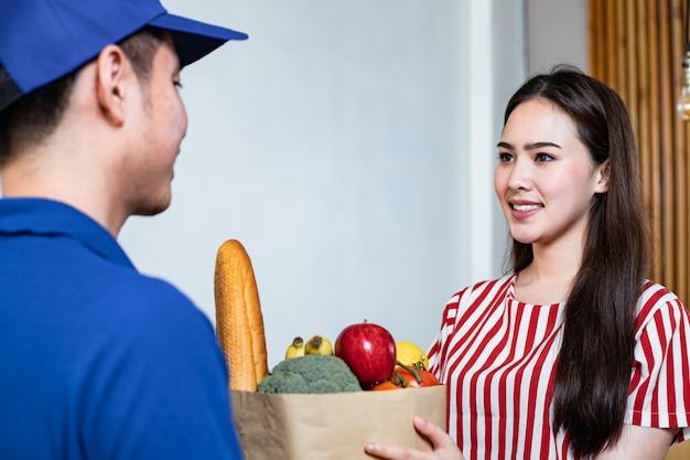 Молодая женщина получает еду из синей униформы, сотрудники службы доставки еды на дом с улыбкой.