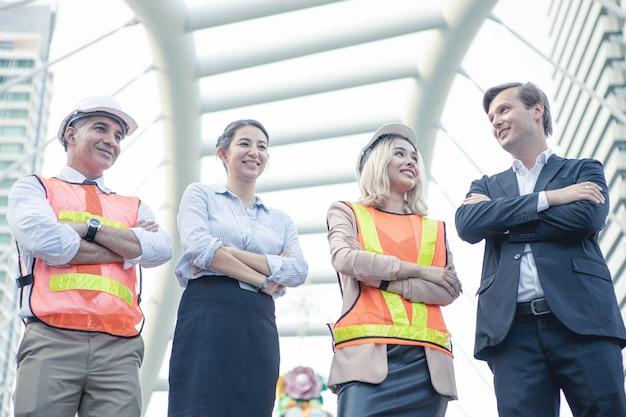 屋外で腕を組んで成功したビジネスマンやエンジニアのグループ。