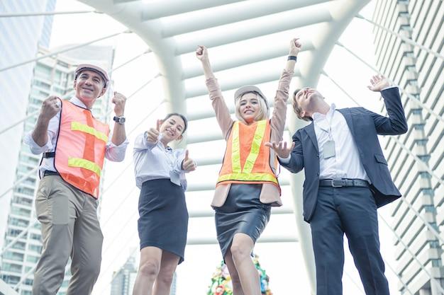 屋外で陽気なビジネスマンやエンジニアの成功したグループ。