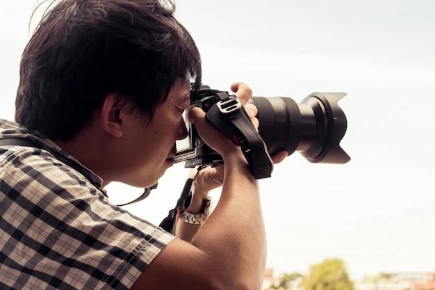 バックパックを着用し、カメラを保持している男性。