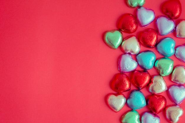 Красный фон с разноцветными сердечками