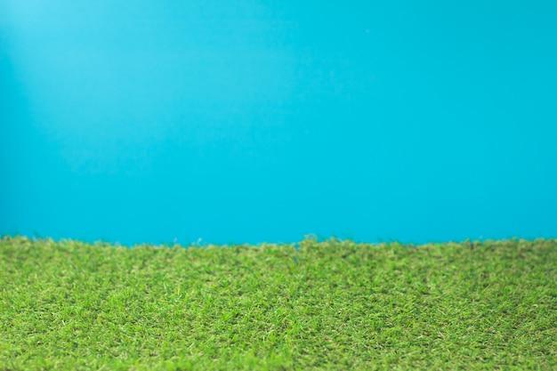 Синий фон и искусственная трава зеленая.
