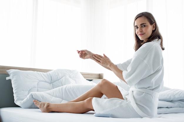 白いベッドの上の彼女の腕にボディクリームを適用する女性。