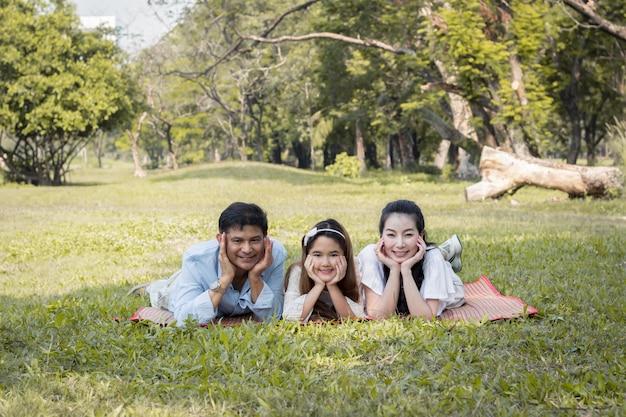 マットの上に横たわっているアジアの家族。