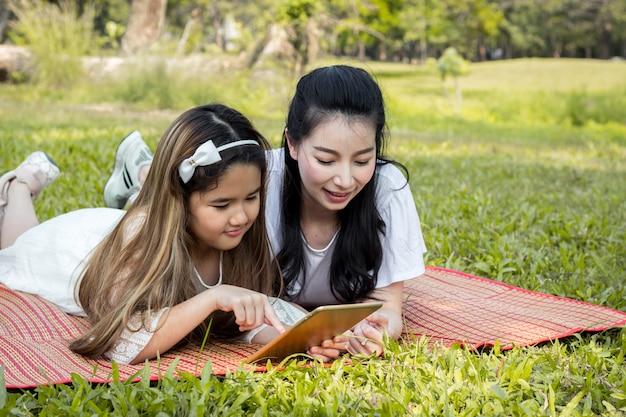 Мама и дети играют в планшет на коврике.
