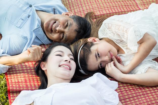 Азиатская семья лежит на коврике.