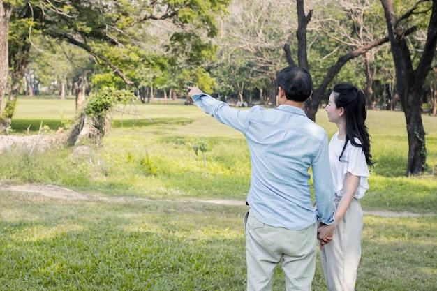 Пары взрослого мужчины и женщины в парке.