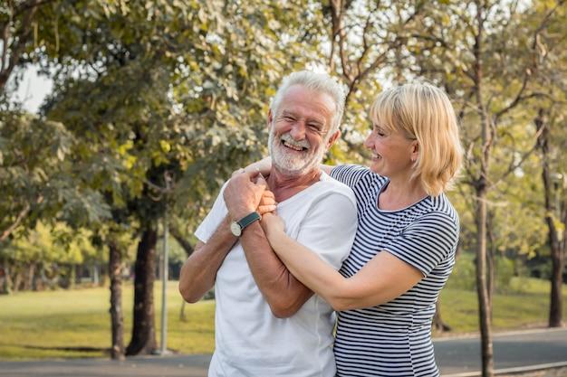 休日に公園で年配のカップルの幸せな笑顔。