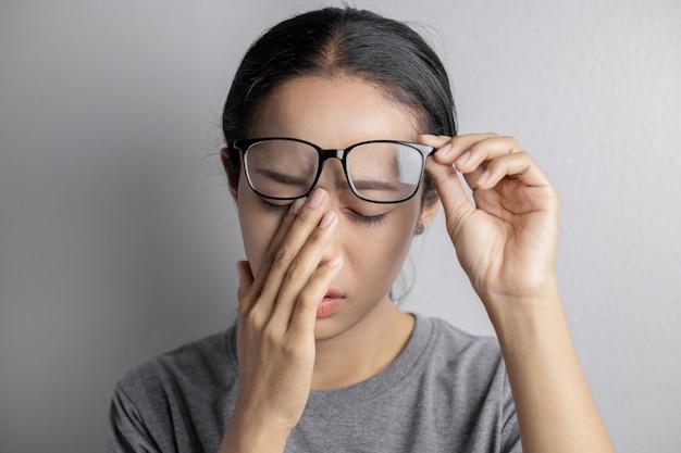 女性は眼鏡を持ち、目の痛みに苦しんでいます。