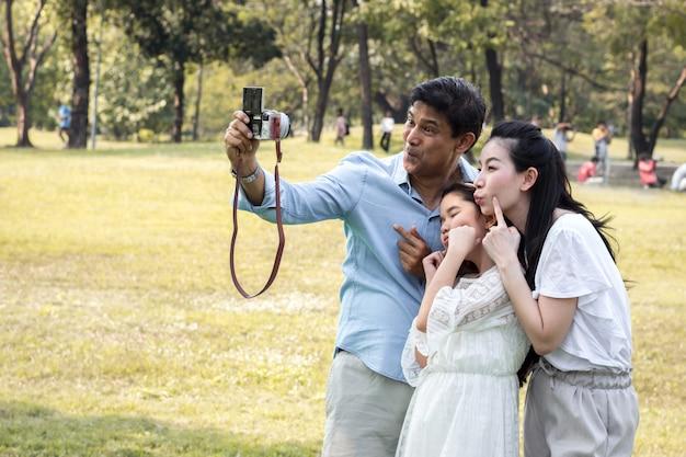 Азиатские семьи делают семейные фотографии в общественном парке.