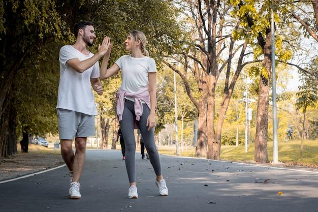 若いカップルが公園でジョギングします。