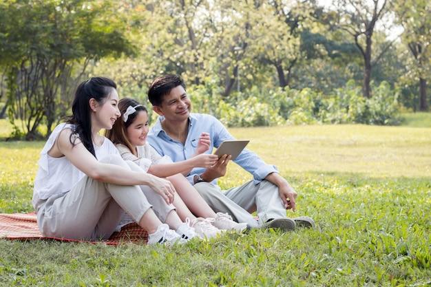 Родители и дети играют в планшет на коврике в парке.