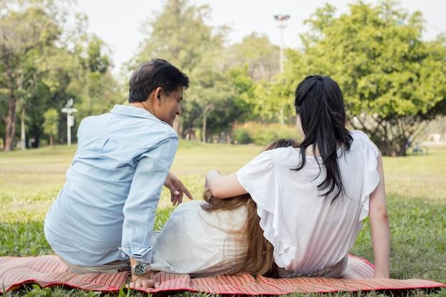 親と子の後ろで公園のマットで遊んでいます。