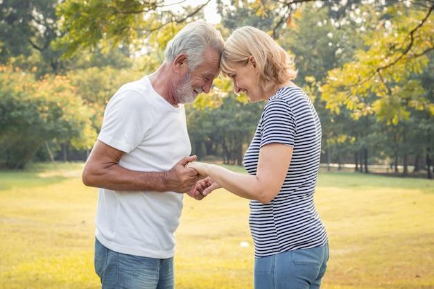 年配のカップルに立って手を繋いでいると笑みを浮かべてします。