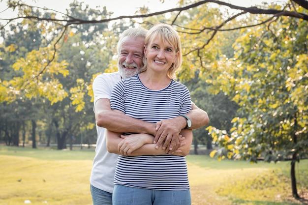 年配のカップルは、お互いを抱きしめ、幸せに笑顔で立っています。
