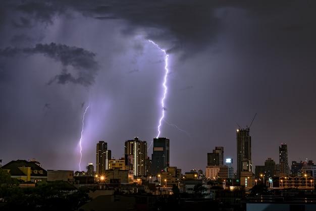 アジアのバンコクで夜の街のスカイラインに雷雨の雷