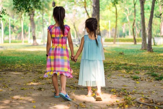 手を握って、夏の緑豊かな公園で一緒に歩く二人の少女の背面図です。