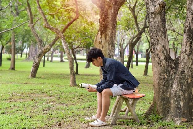若い男は座ってリラックスして、公園で本を読んでいます。