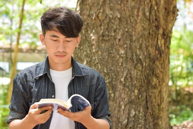 庭の木に戻って、自然の中で本を読んでリラックスした若者