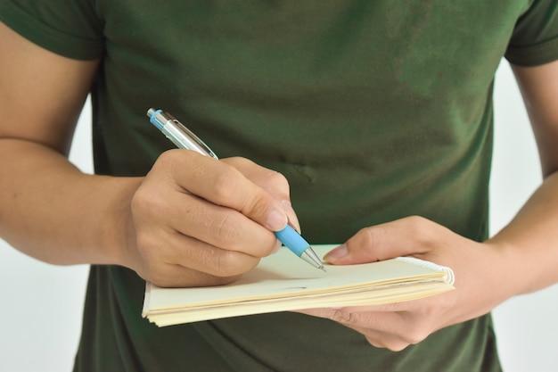 ノートを作る準備ができているペンを持っている男性の手