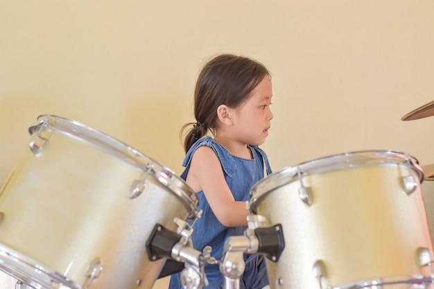 Конец-вверх молодой азиатской девушки играя барабанчик.