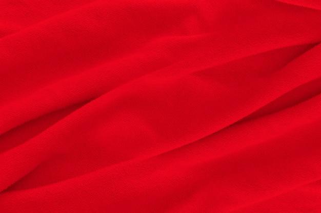 赤い布のテクスチャの背景。柔らかい波と抽象的な布の背景。