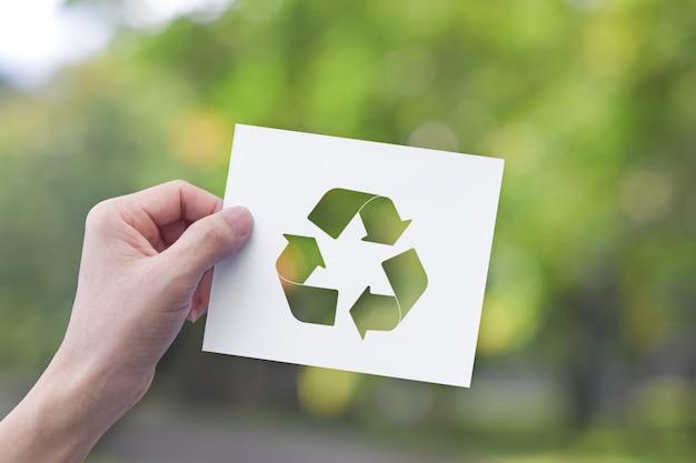 リサイクルシンボルとホワイトペーパーを持っている手