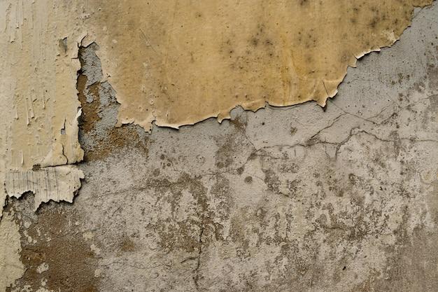 背景として金セメント表面で覆われたひび割れたコンクリート壁