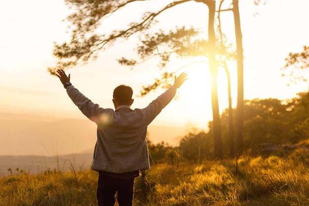 人は山の頂上で夕日の間に空中に手を上げる