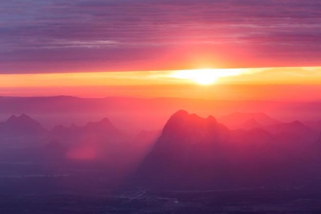ソフトフォーカスとぼやけ夜明けの太陽と山の頂上に美しい風景