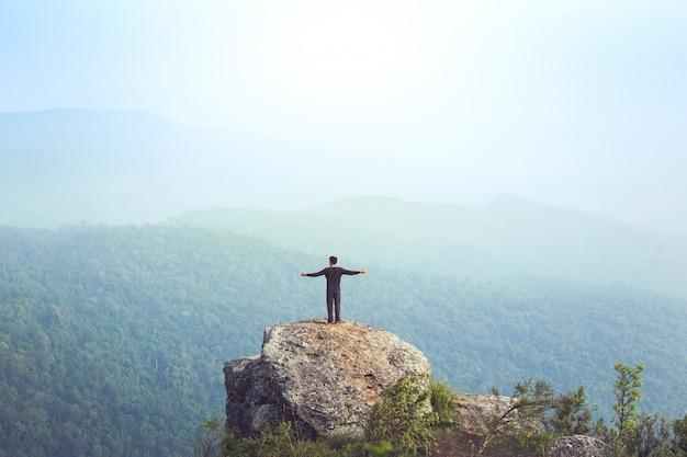 Молодой человек турист азии на горе наблюдает за туманным и туманным утренним восходом солнца