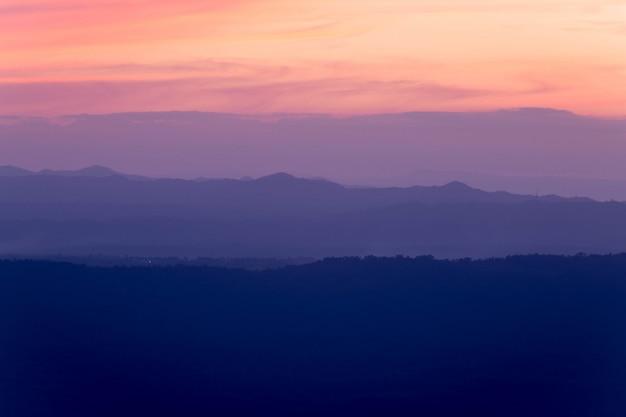 朝の霧の中で山の丘の層のシルエット。カラフルな夏のシーン。