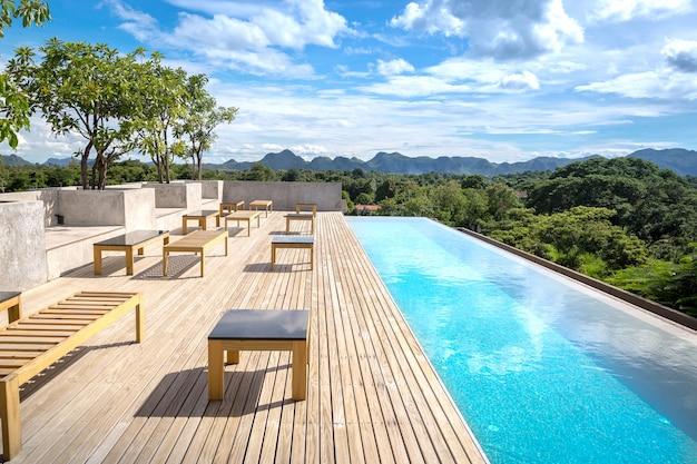 Плавательный бассейн на крыше здания палубы и солнечные блики с полосами тикового дерева летние каникулы