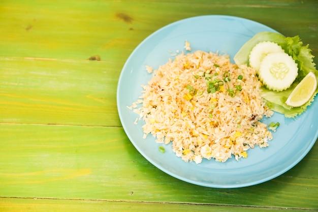 緑のテーブルに置かれた皿の中のカニの揚げた米。