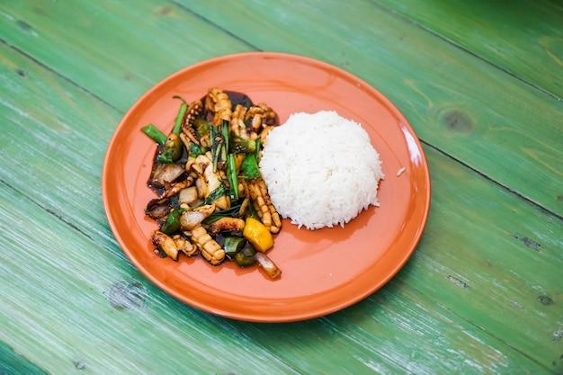 イカ卵と炊飯米を入れたスパイシーなサラダを緑色のテーブルに置いた。