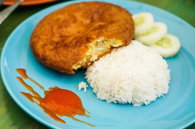 グリーンテーブルに置かれた青い皿に豚肉とふわふわのオムレツを入れた蒸し米。