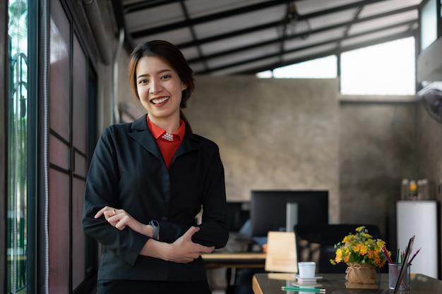幸せな女性実業家のワークステーションに笑みを浮かべてください。
