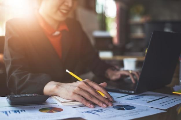 ペンを持っていると金融書類を指して実業家の手を閉じます。