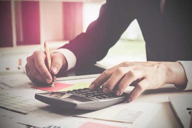Закройте вверх по ручке удерживания руки бизнесмена и делать финансы и высчитайте на деревянном столе о офисе цены дома. концепция бухгалтера. винтаж.